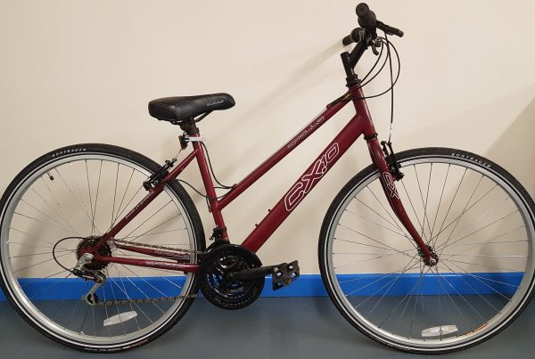 Ladies hybrid bicycle in deep red colour pictured against plain background